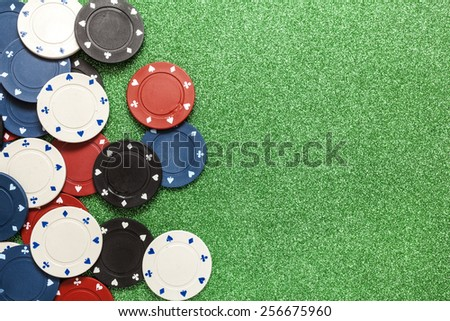 Poker chips isolated against a green background  - stock photo