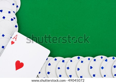 Poker chips making a border on a green background, playing poker