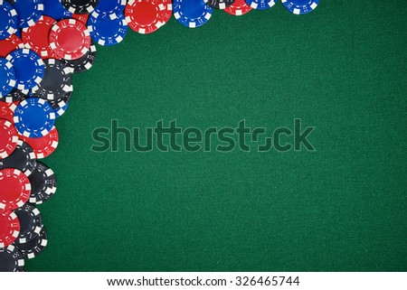 Poker chips on green table in casino - stock photo