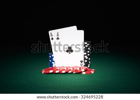 Poker chips on table with aces cards in casino with black background - stock photo