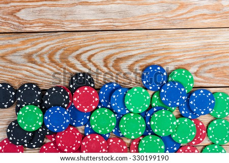 Poker chips over old wooden table. Frame of poker chips. Casino background.