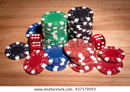 Poker chips over old wooden table. Group of different poker chips. Casino background.
