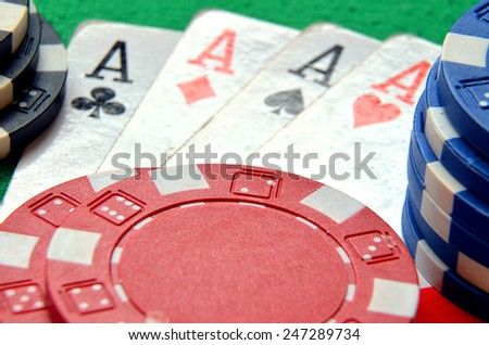 Poker chips pile and aces detail on green table - stock photo