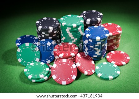 poker chips stack on green table, black background