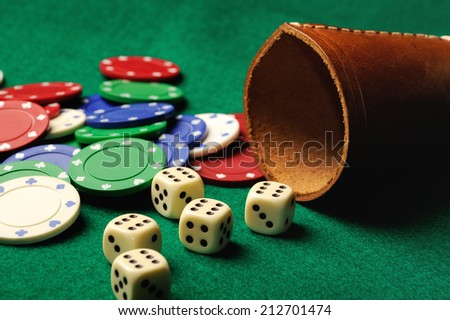 Poker dice with chips on green casino table - stock photo