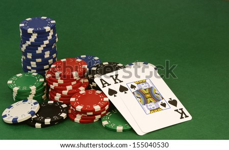 poker hand - ace and king of spades in front of chips - stock photo