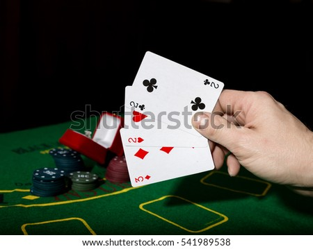 poker on a green table background, man holding losing combination of cards
