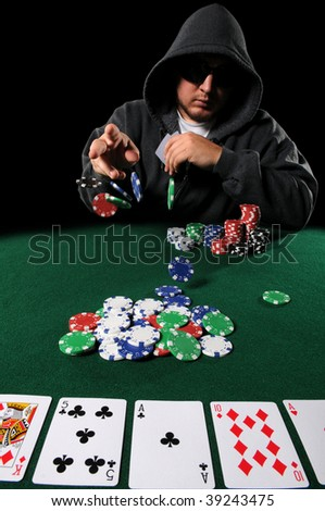 Poker played with hood and sunglasses throwing chips on stack - stock photo