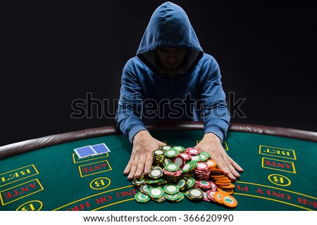 "Poker player going ""all in"" pushing his chips forward - stock photo"