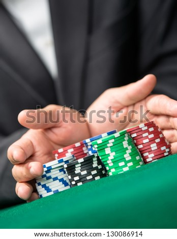 "Poker player going ""all in"" pushing his chips forward. Challenge to the casino - stock photo"
