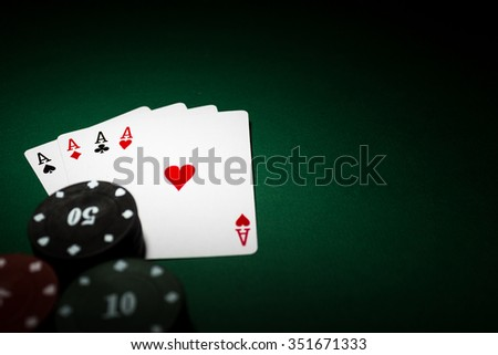 poker player holding 4 Ace of pokers beside lots of chips