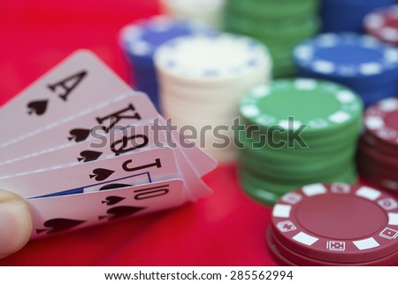 poker player holding 10 to Ace spade straight flush of pokers beside lots of chips - stock photo