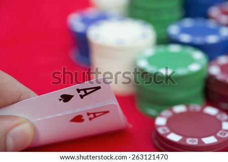poker player holding two aces beside lots of chips - stock photo