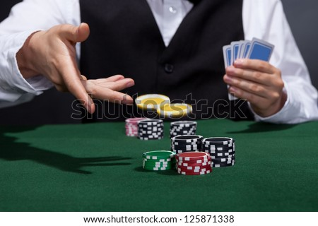 Poker player increasing his stakes throwing tokens onto the gaming table to meet or beat his opponents wager to stay in the game - stock photo