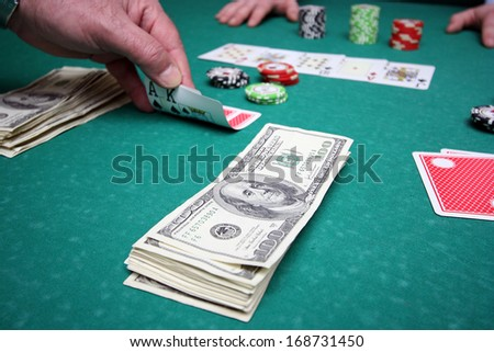 poker player lifting the corners of two cards in casino. - stock photo