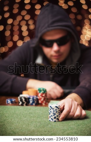 Poker player / Raising bet in a casino - stock photo