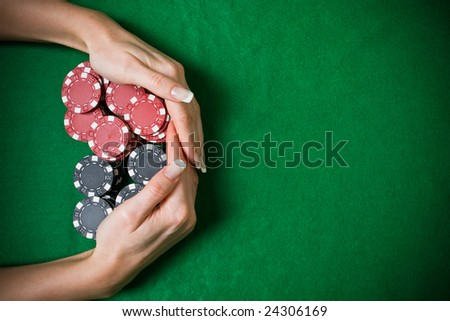 Poker player raking a big pile of chips - stock photo