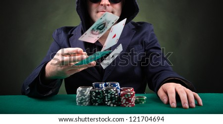 Poker player throwing cards on black background
