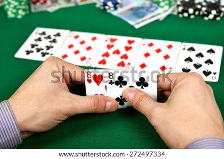 poker player with two eights and chips at green casino table - stock photo