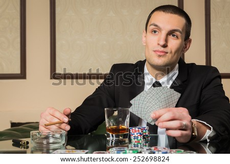 Poker player. Young guy in the casino at the gaming table. Man gambling, card games. Cards, chips, whiskey, cigarettes, poker, card game, gambling - gambling concept. - stock photo