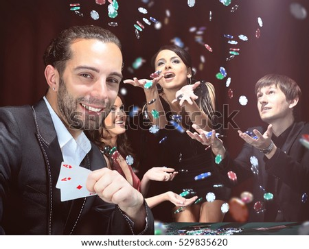 Poker players sitting around a table at a casino