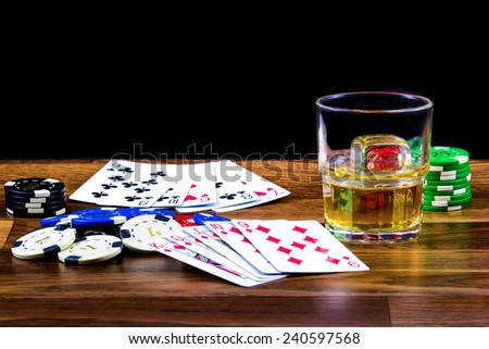 Poker scene with drink on a dusty wooden table - stock photo