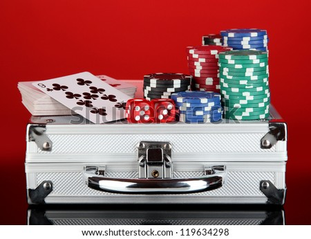 Poker set on a metallic case on bright red background - stock photo