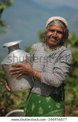 POKHARA, NEPAL - APRIL 28: Nepalese woman in national clothes with jug in Pokhara, Nepal on April 28, 2013.  Due to its proximity to the Annapurna mountain range, Pokhara is also a base for trekkers.