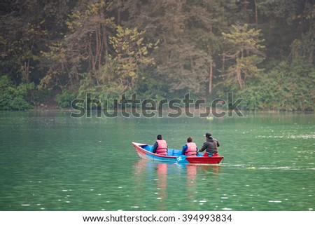 POKHARA, NEPAL - DEC 19: Unidentified tourists in colourful wooden boat at Fewa lake on December 19, 2015 in Pokhara, Nepal. Pokhara is the major tourism Hub known for trekking and boating.