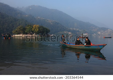 POKHARA, NEPAL - FEB 06: A boatman transport a couple through the Fewa lake in the on February 06, 2014 in Pokhara, Nepal. Pokhara is a popular tourist destination known for trekking and boating.