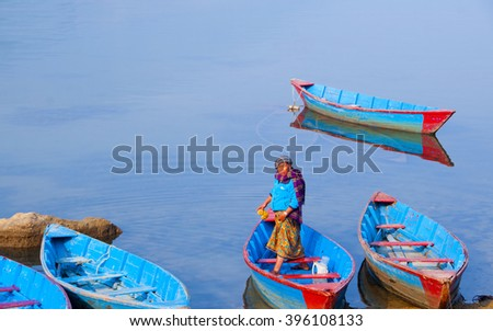 POKHARA, NEPAL - FEB 6 : Unidentified tourists in colourful wooden boat at Fewa lake on February 6, 2014 in Pokhara, Nepal. Pokhara is the major tourism Hub known for trekking and boating.