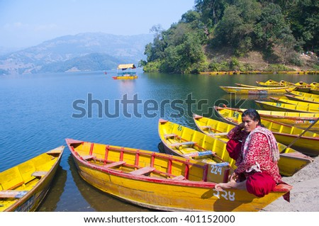 POKHARA, NEPAL - FEB 6 : Unidentified woman in colourful wooden boat at Begnas lake on February 6, 2014 in Pokhara, Nepal.