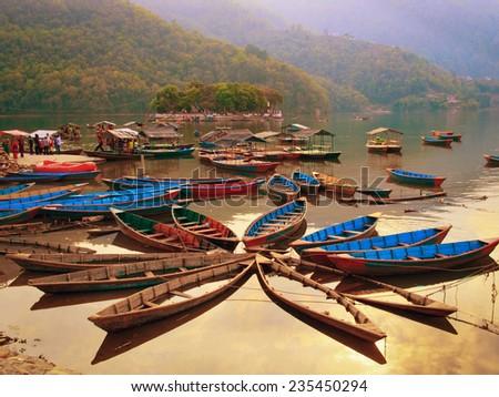 POKHARA, NEPAL - MARCH 30: Unidentified tourists do boating on Fewa (Phewa) lake on March 30, 2014 in Pokhara, Nepal. Pokhara is a popular tourist destination in Nepal. - stock photo