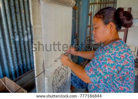 POKHARA, NEPAL - OCTOBER 06 2017: Close up of unidentified woman working on loom manufacturing wool shawl clothing in Nepal