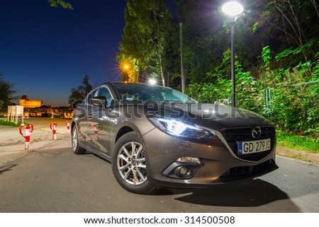 POLAND-AUGUST 9, 2015: New Mazda 3 captured at dusk with long exposure technique. Mazda 3 is a popular compact car manufactured in Japan by the Mazda Motor Corporation. - stock photo