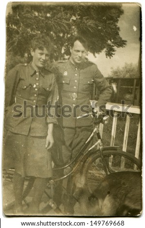 POLAND - CIRCA end of 1940s: Antique phoro shows woman and a man with a bike is the soldiers of the Polish Army, end of 1940s