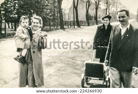POLAND, CIRCA FIFTIES: Vintage photo of family with little daughter and pram - stock photo