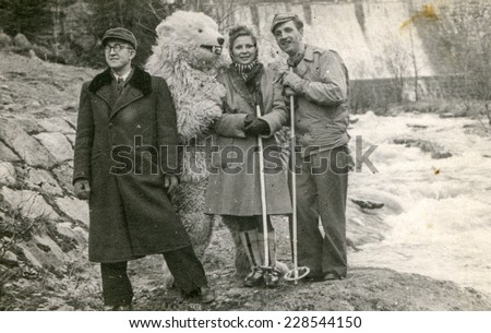 POLAND, CIRCA FIFTIES: Vintage photo of two men and a woman posing with a fake bear