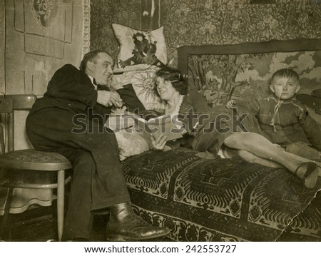 POLAND, CIRCA THIRTIES: Vintage photo of a woman reading a book on bed, with her husband and little son