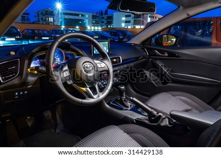 POLAND-SEPTEMBER 24, 2014: Interior of new Mazda 3 captured at dusk with long exposure technique. Mazda 3 is a popular compact car manufactured in Japan by the Mazda Motor Corporation. - stock photo