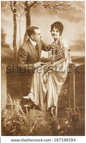 POLAND, WARSAW - CIRCA 1924 : old photo  of happy young romantic couple of woman and man in spring garden. Illustrative Image, subject of human interest