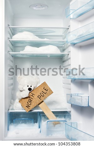 Polar bear in refrigerator with North Pole sign. Global warming problem - stock photo