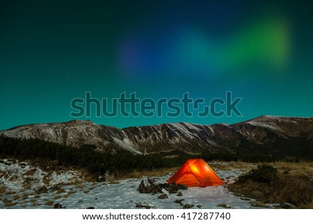 Polar Night landscape with illuminated tent and Polar Lights, Silhouettes of snowy mountain peaks night sky with many stars and Northern Lights on background illuminated orange tent on foreground - stock photo