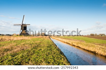 Polder mill with a scoopwheel in a Dutch polder landscape in low afternoon sunlight  in the winter season.