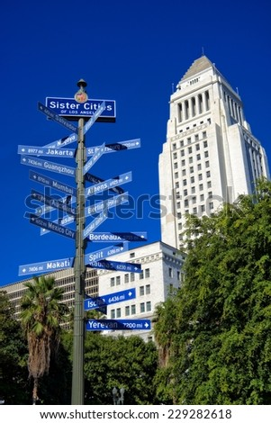 Pole and street signs indicating the direction and distance to many sister cities of Los Angeles around the world. In the back, the Los Angeles City Hall building. - stock photo