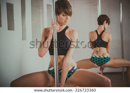 Pole Dance. Gymnast coached exercises on pole