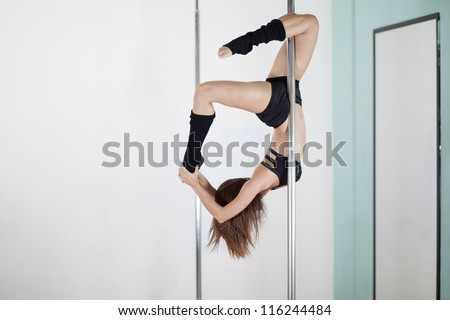 Pole fitness instructor practicing a difficult pose