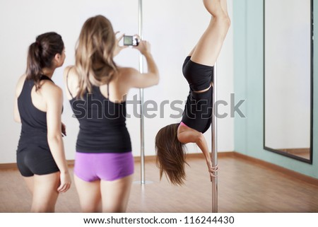 Pole fitness students taking a picture of their instructor during a demonstration