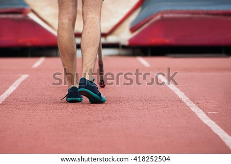 Pole vaulter prepares for jump,looking from behind
