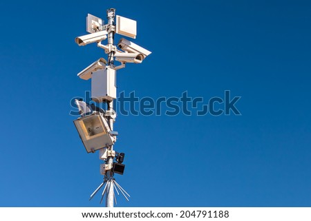 Pole with different security cameras and motion sensors against a clear blue sky - stock photo